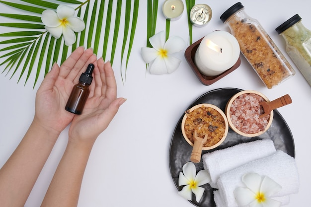 Hands of a beautiful woman holds a bottle of serum. pine essential oil. spa treatment and product for female hand spa, massage and candles, relaxation. flat lay. top view.