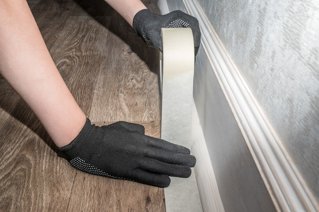 Hands in black gloves gluing tape to wood panels. renovation in the apartment.