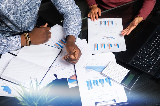 Hands of black people and financial documents in business space close-up