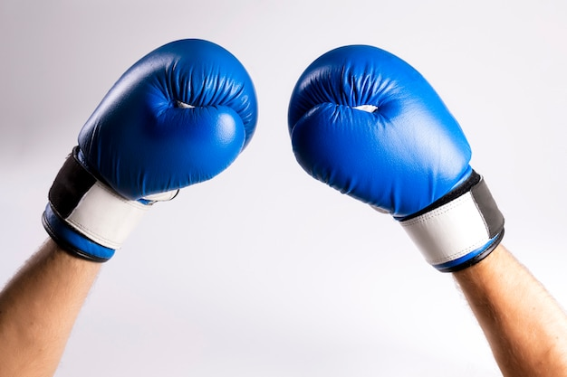 Hands in blue boxing gloves raised up, symbol of victory in battle