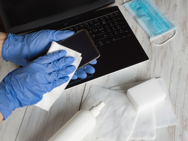Hands in blue gloves wipe smartphone screen with disinfectant cloth from bacteria and viruses