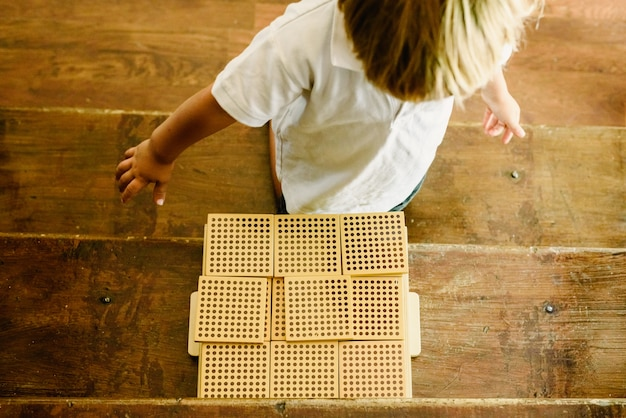 Hands of boy manipulating counting cubes on wooden background in montessori classroom
