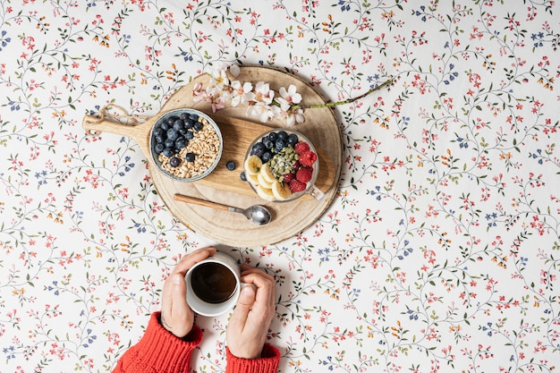 The hands of a boy with a cup of coffee and yogurt with fruits on a bed. copy space