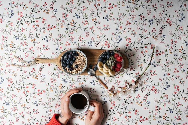 The hands of a boy with a cup of coffee and yogurt with fruits on a bed