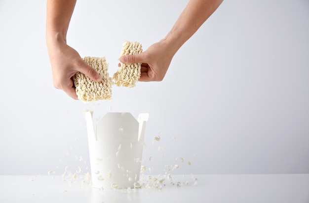 Hands break pressed pack of dry noodles above opened blank takeaway box before preparation. commercial retail promo set