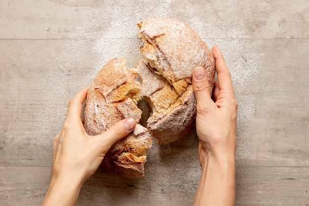 Hands breaking a delicious bread
