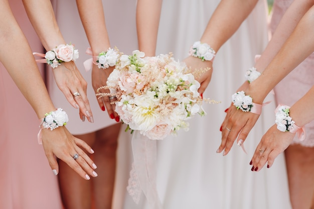 Hands of the bride and bridesmaids with flowers in pink shade