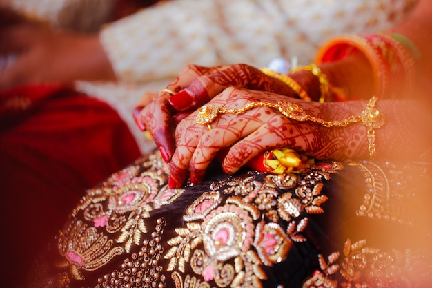 Hands of bride decorated with beautiful mehndi art along with jewelry and colorful bangles