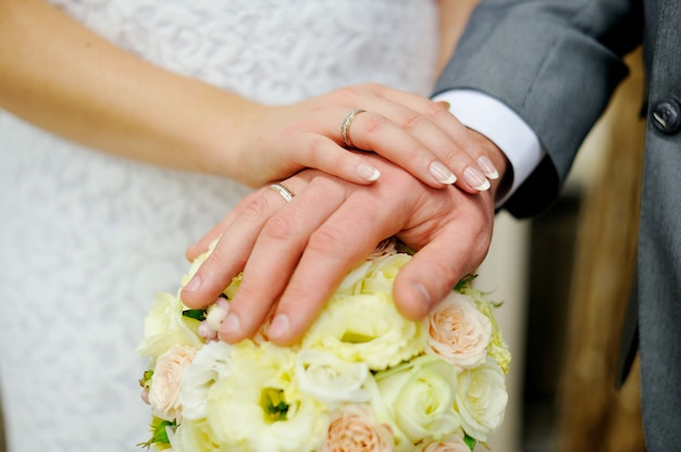 Hands of bride and groom on the bouquet roses.