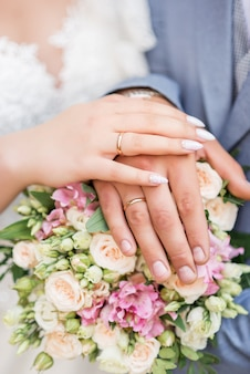 Hands of the bride and groom close up, wearing white gold wedding rings on her hands