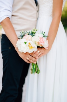 Hands of bride and groom holding wedding bouquet close up