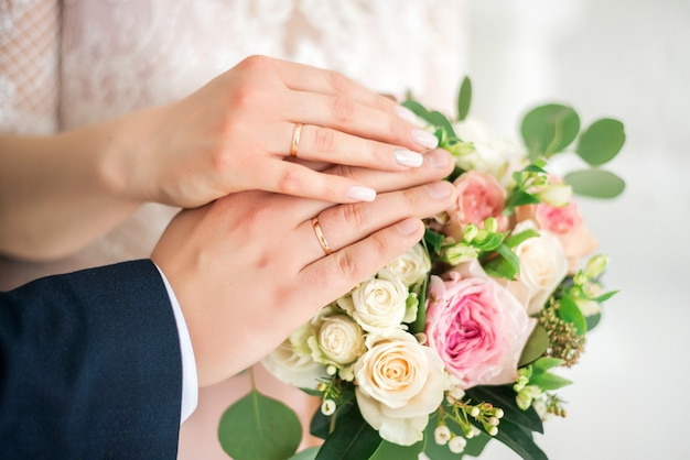 Hands of the bride and groom wearing white gold wedding rings on their hands