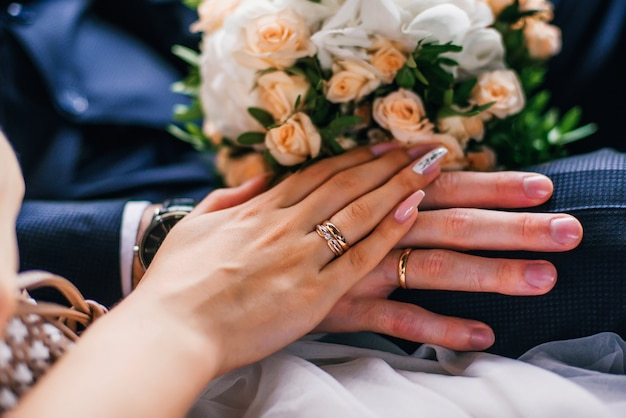 Hands of the bride and groom with gold rings on the wedding day together