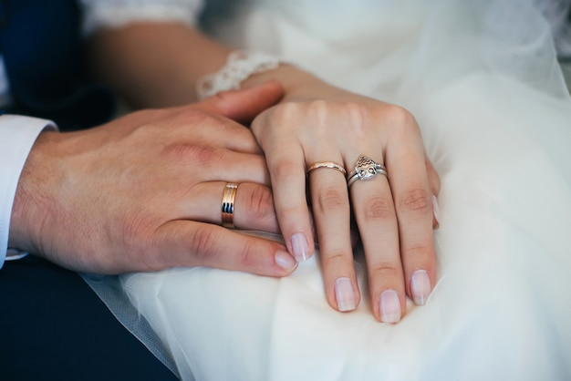 Hands of bride and groom with gold wedding rings on white dress