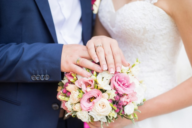 Hands of bride and groom with rings on wedding bouquet. marriage and love concept