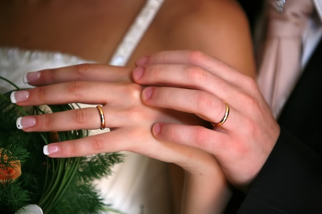 The hands of the bride and groom with the rings