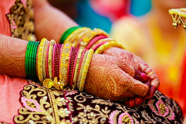 Hands of bride is decorated beautifully by indian mehndi art along with jewelerys and colorful bangles