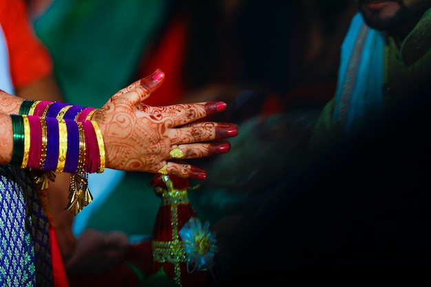 Hands of bride is decorated beautifully by indian mehndi art along with jewellery