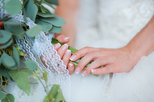 Hands of a bride, just married, a bridal bouquet is beside