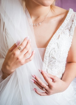 The hands of the bride with gold wedding ring with a diamond. bride's preparations. wedding morning. jewelry. manicure close up. engagement. the buttonhole with flowers.