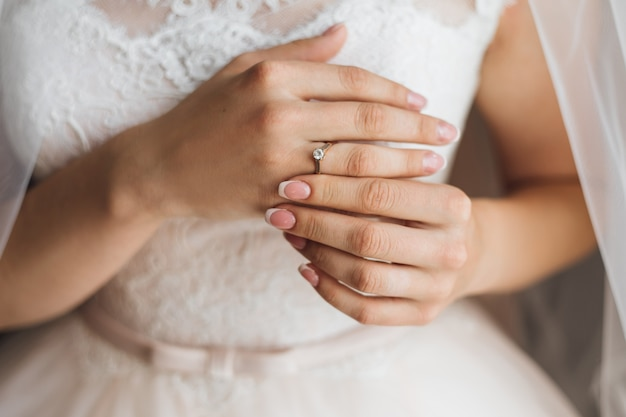 Hands of a bride with tender french manicure and precious engagement ring with shiny diamond, wedding dress