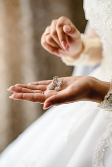 Hands of the bride with wedding earrings