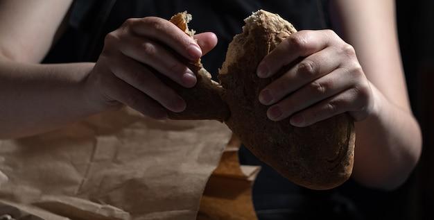 Руки ломали аппетитный свежий хлеб, вынутый из бумажного пакета. темный фон.