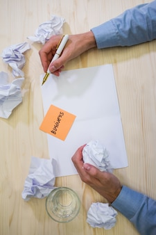 Hands of business executive holding crumpled paper and pen