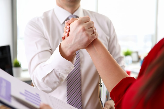 Hands of businessman and businesswoman in official clothing standing in office and making agreement by handshake, close-up. business people, negotiations, people working in office concept