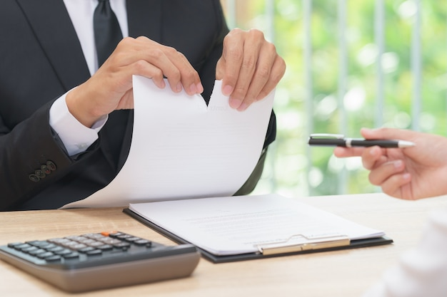 Hands of businessman ripping agreement paper when woman giving a pen for signing, break th