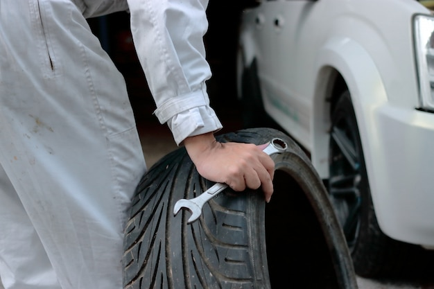 Hands of car mechanic in uniform holding wrench and tire at the repair garage background.