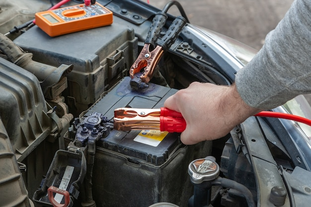 Hands of car mechanic using car battery jumper cable to start-up engine