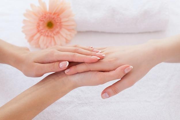 Уход за руками. крупный план массажиста, массирующего руки клиентки