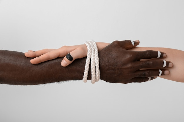 Hands of caucasian woman and african-american man tied together with rope on light background. racism concept