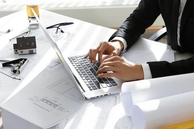 Mani del ceo della società di costruzioni in abito nero digitando un messaggio via e-mail ai partner sul laptop con disegni, timbro sigillo, divisore sul tavolo.