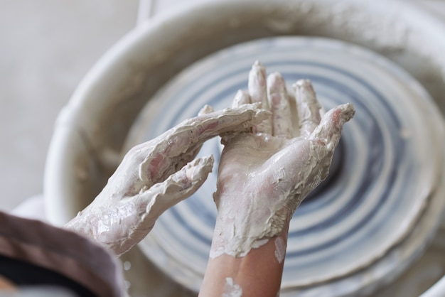 Hands of ceramist covered in clay after working on potters wheel