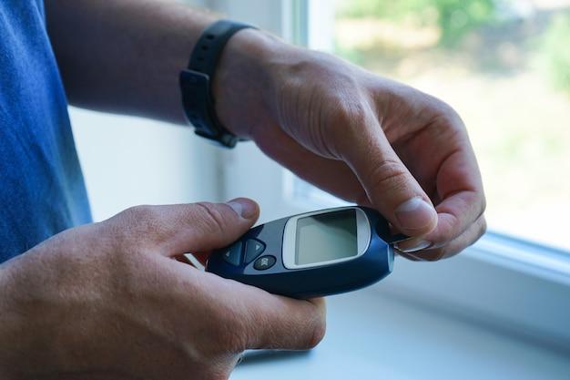 Руки проверяют уровень сахара в крови с помощью глюкометра