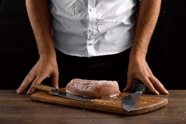 Hands of the chef close-up on the table, a piece of meat, a kitchen knife