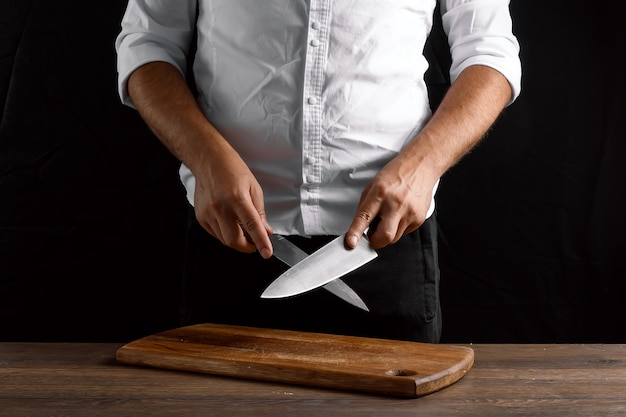Hands of the chef closeup sharpens a kitchen knife on a knife