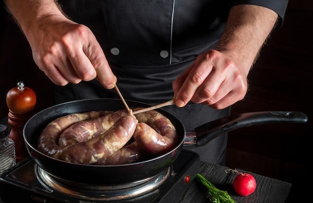 수제 소시지의 실을 묶는 요리사 또는 요리사 고기와 향신료로 소시지 요리하기