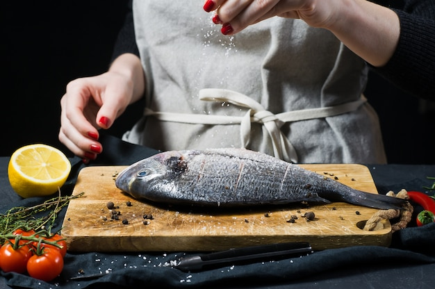 Hands chef salted dorado fish on a wooden chopping board