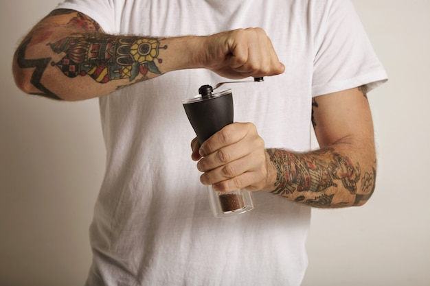 Hands and chest of a tattooed young man grinding coffee in a manual burr grinder
