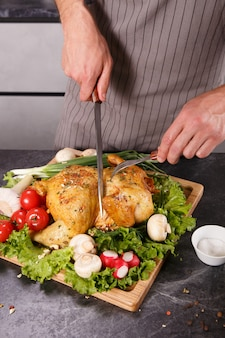 Hands of chief man cuting baked chicken with vegetables