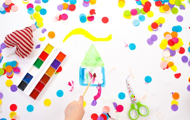 The hands of a child drawing with watercolors on a white background on top. colorful confetti. close-up