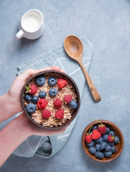 手の子供は青い背景にエネルギーグラノーラとベリーとココナッツボウルを保ちます。エネルギーとビーガンの朝食。上面図