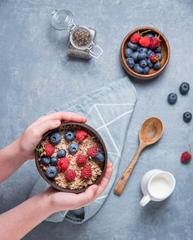 Hands child keep coconut bowl with muesli and berries on blue