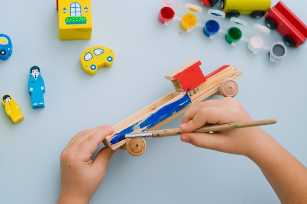 Hands of a child paint a wooden machine