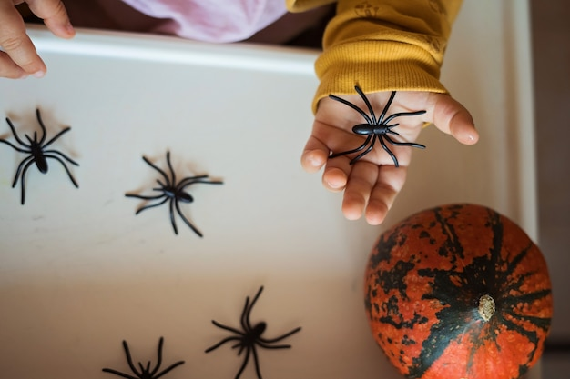 Hands of a child playing with black rubber spiders toys. halloween