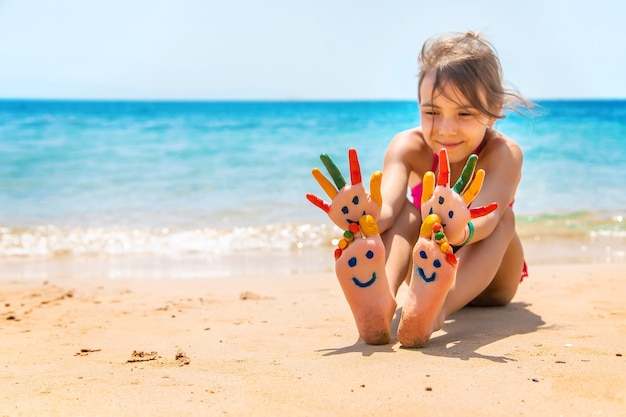On the hands of the child, a smile with paints on the sea