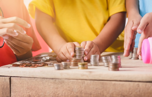 Hands of children are helping putting coins into piggy bank on white